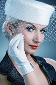 Beautiful young woman in white hat with net veil. Retro portrait poster