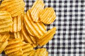 Crinkle cut potato chips on checkered tablecloth. Tasty spicy potato chips. poster