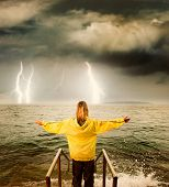 Brave woman greeting stormy ocean