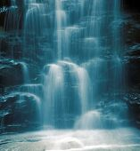 a close-up of a beautiful waterfall with a blue cast to it for effect. very cooling and peaceful feel. nice background image. poster