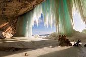 Grand Island in Winter - Lake Superior. A stump is the highlight in this cavern behind the Grand Island ice curtains on Lake Superior near Pictured Rocks National Lakeshore in Munising Michigan poster