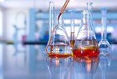 science laboratory glassware orange solution drop to flask poster