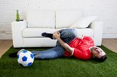 fanatic football fan lying on green grass carpet emulating soccer stadium pitch mocking player in pain hurt on ankle while watching game on television in crazy supporter parody concept poster