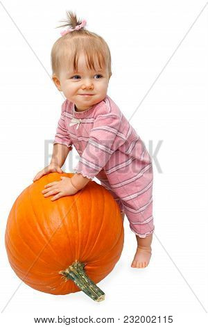 An Adorable Toddler Girl In A Striped, Pink Jumper Leans On A Large Pumpkin.  Her Hair Is Tied Up In