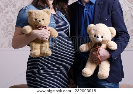 Pregnant Wife And Husband Hold Bears In Hands