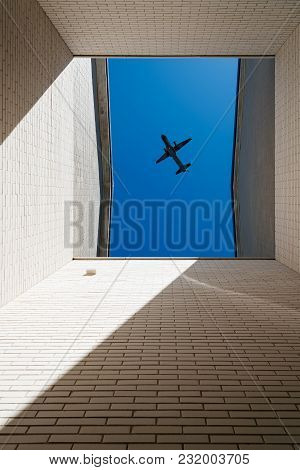 Plane Flying Above Courtyard Of Modern Architecture Brick Building.