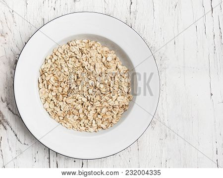 Oatmeal, Rolled Oats On White Wooden Table. Porridge Oats, Used In Granola Or Muesli. Copyspace, Fla