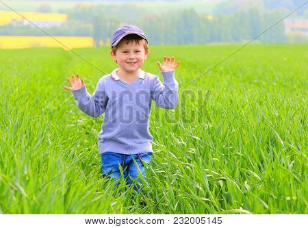 A country boy playing in green wheat field. Happy life on Czech countryside. People and sustainable development in European Union.