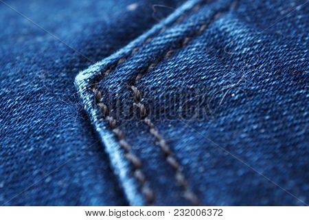 Denim Fabric Blue Macro. Texture Jeans With Stitched Seams.