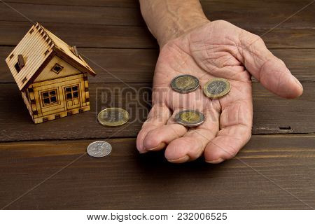 Old Man Hands And A Model Home With The Coins On The Table .the Concept Of Mortgages And Bank Loans.