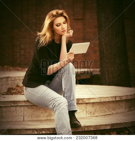 Young fashion blond business woman using tablet computer on city street