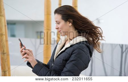 Selfie, Brown-haired woman in video conference with the mobile. talking on the street with your partner through the use of new technologies