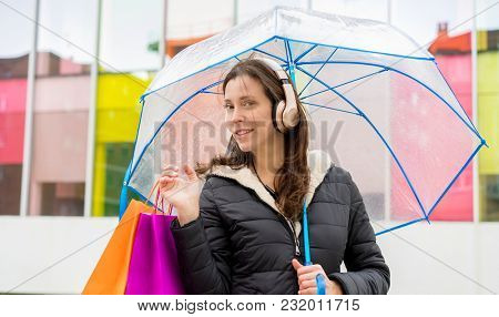 shopper. Brown-haired woman shopping. carry colorful bags with purchases and a transparent umbrella