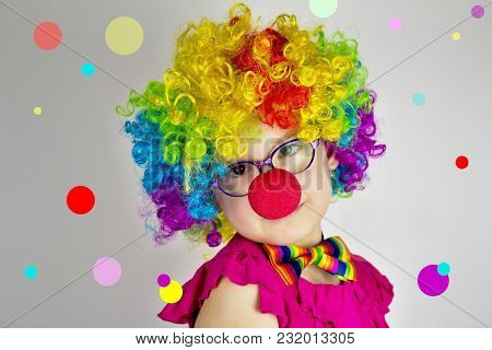 Little Girl In Clown Costume In Front Of  Background With Colorful Dots.little Girl With Glasses In