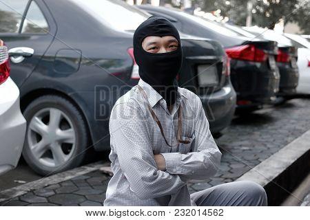 Masked Burglar Wearing A Balaclava Ready To Burglary Against Car Background. Insurance Crime Concept