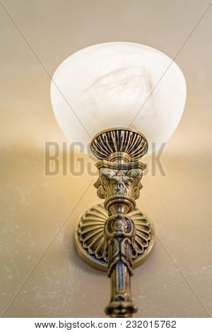 Brass Sconce With Lighting Bulb On White Wall
