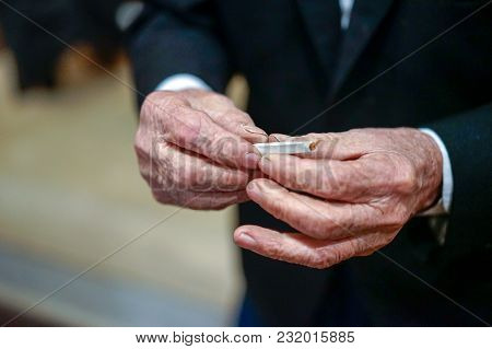 Old Man Hand Made Cigarette Rolling With Dried Smoking Tobacco And White Paper