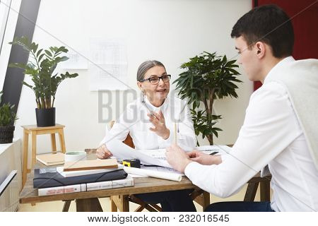 Cheerful Positive Mature Female Boss In Stylish Eyewear Holding Engineering Blueprints Of Talented S