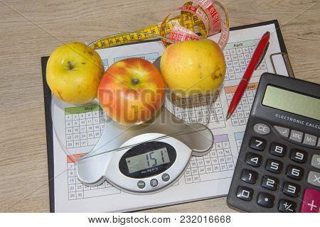 Apple With Measuring Tape, Calculator, Libra. Fruit Diet. The Concept Of Dieting, Losing Excess Weig