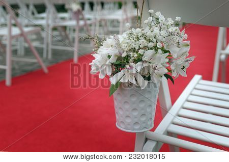 Wedding Chair Decorated With Lilies, Alstroemerias And Chrysanths Flowers Behind The Red Carpet. Bea