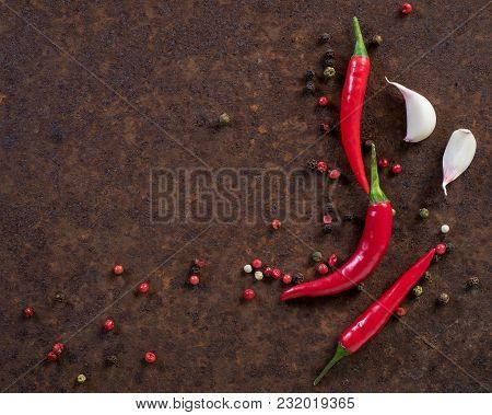 Red Hot Chili Pepper Pods And Peas, Garlic Clove On Dark Rusty Metal Background, Top View, Copy Spac