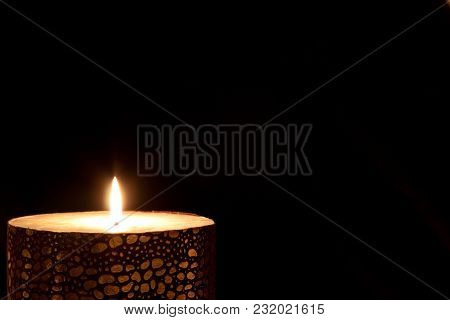 A Glowing Candle On The Dark Isolated
