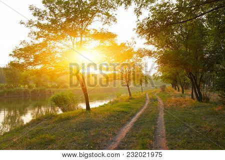 Rural Landscape, Rural Road Along The River Between The Trees At Sunset