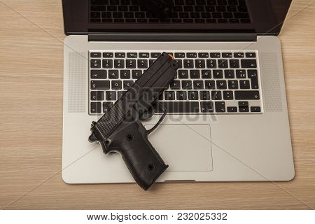 Conceptual Photo, Weapon On A Laptop As A Symbol Of Organized Crime Operating On The Internet, Top V