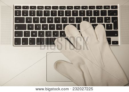 Conceptual Photo, The Glove On The Keyboard Shows The Possibility Of Not Tracking Down Online Crime,