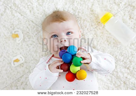 Cute Adorable Newborn Baby Playing With Colorful Wooden Rattle Toy, Nursing Milk Bottle And Dummy. N