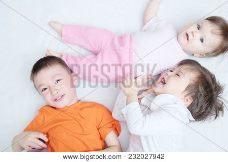 Happy Laughing Kids, Three Children Different Ages Lying, Portrait Of Boy, Little Girl And Baby Girl