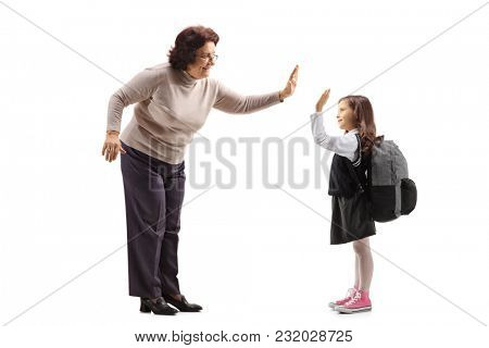Full length profile shot of an elderly woman high-fiving a schoolgirl isolated on white background