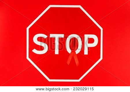 Red Tape As Symbol Of Aids / Hiv Illness Lying With Red Stop Road Sign Isolated On Red Background