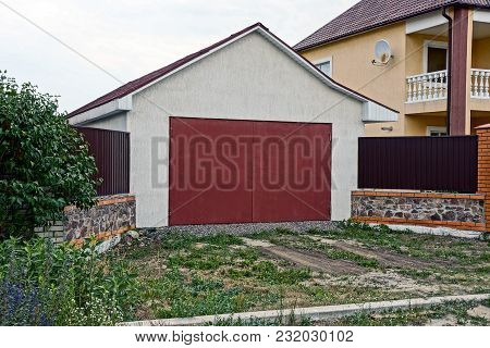 Facade Of A Private Garage With Red Gates