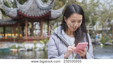 Woman use of smart phone in chinese garden