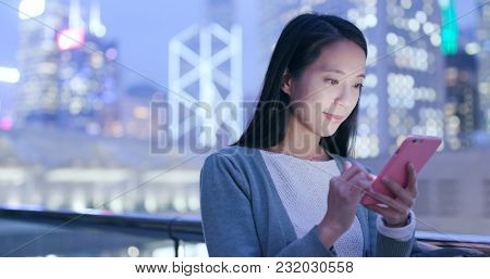 Woman use of mobile phone in city at night