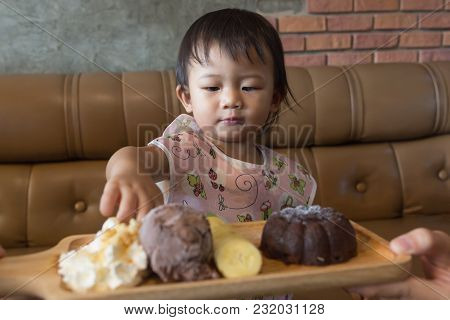 Asian Cute Baby Girl Enjoy Eatting Chocolate Lava Set In The Cafe