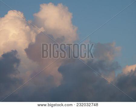 Cumulus clouds in rays of sun poster