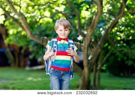 Happy Little Kid Boy In Colorful Shirt And Backpack Or Satchel On His First Day To School Or Nursery
