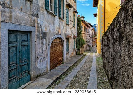 Narrow cobblestone street among old houses in small town of Orta San Giulio in Piedmont, Northern Italy.