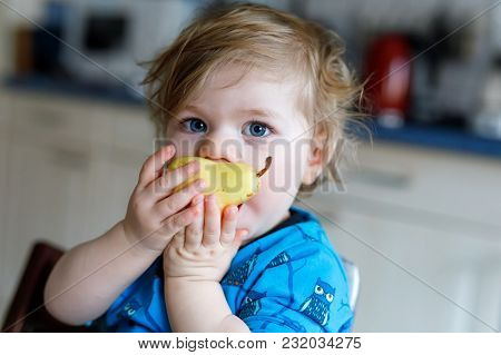 Cute Adorable Toddler Girl Eating Fresh Pear . Hungry Happy Baby Child Of One Year Holding Fruit. Gi