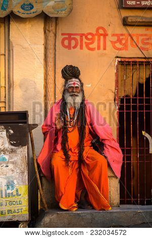 VARANASI, INDIA - MAR 19, 2018: Sadhu or Baba (holy man) on the ghats of Ganges river. Normally a sadhu is a monk, renounced, renounced material enjoyment.