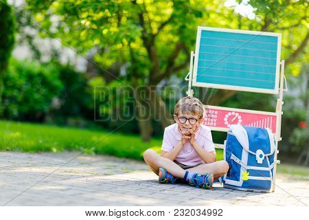 Happy Little Kid Boy With Glasses Sitting By Desk And Backpack Or Satchel. Schoolkid With Traditiona