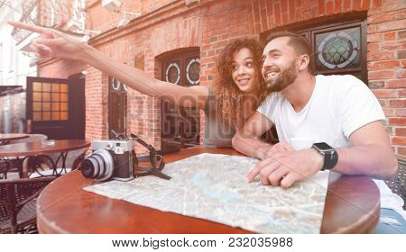 Young  tourists drinking coffee at cafe and reading city map