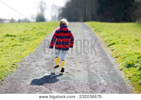 Little Kid Boy Wearing Yellow Rain Boots And Walking On Nature Path On Warm Sunny Spring Day. Happy