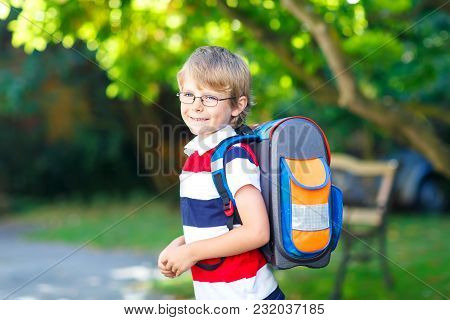 Happy Little Kid Boy With Glasses And Backpack Or Satchel On His First Day To School Or Nursery. Chi