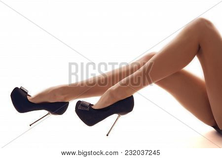 Beautiful Woman Legs Wearing A High Stiletto Heels Isolated On A White Background.