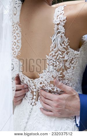 Detail Of The Back Of The Bride On Her Wedding Day While In Her Husband She Grabs Him By The Waist
