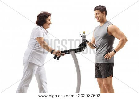 Elderly woman exercising on a treadmill with a personal trainer isolated on white background