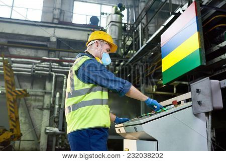 Side View Portrait Of Young Factory Worker Wearing Hardhat And Protective Mask Operating Machine Uni